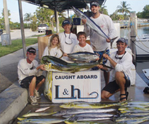 family holding caught fish in front of L&H sign